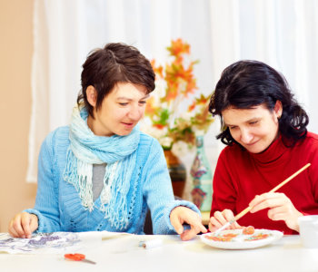 happy adult women with special needs doing handcraft